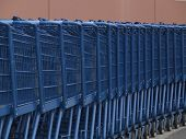 line of blue grocery carts outside market poster