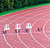 Lanes one through 3 equipped with starting blocks for the 100m dash poster