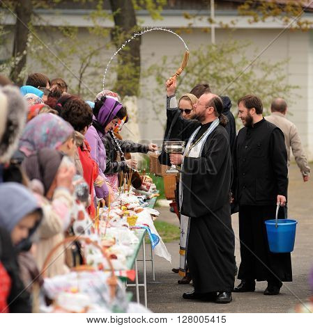 Orel Russia - April 30 2016: Paschal blessing of Easter baskets in Orthodox church. Priest pouring holy water on women square