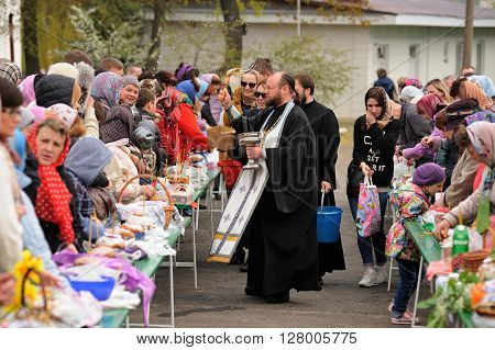 Orel Russia - April 30 2016: Paschal blessing of Easter baskets in Orthodox church. Priest going between rows of people with Easter meals horizontal