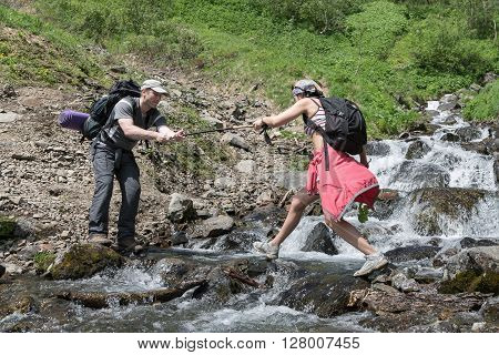 KAMCHATKA RUSSIA - JUNE 23 2012: Summer hiking - tourist man helps a girl-tourist to cross the mountain river in a summer sunny day on the Kamchatka Peninsula. Eurasia Russian Far East Kamchatka Region.