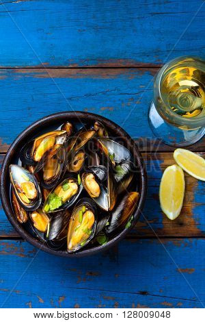 Mussels in clay bowl, glass of white wine and lemon on wooden blue background