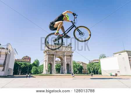 Acrobatic biker jumping with his bicycle on the streets - Bmx bicycle rider tricking outdoors