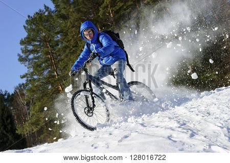 Cyclist riding bike, extreme winter cycling near snowbanks of snowy mountain slope, cross country biking near forest in cool sunny day