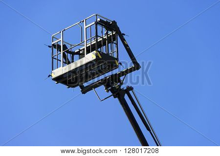 Hydraulic lift platform with bucket of construction vehicle painted in black color with blue sky on background