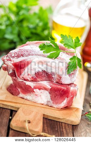 fresh raw meat on wooden board on table