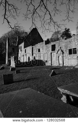 A view across a medieval graveyard toward the ruins of St. Bridgets Kirk