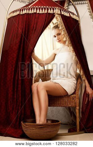 Spa. Pretty young woman takes foot bath in parlour