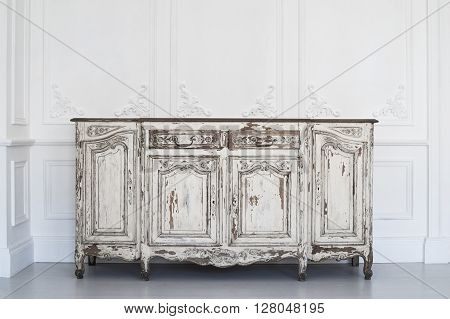 Antique white chest of drawers with fretwork wall on backround