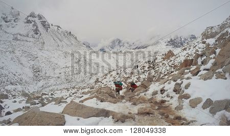Trekkers and porters in mountains, Porters carrying stuff for trekkers, trekking to the mountain Everest base camp, Himalaya mountains, Himalayan landscape during snow storm, storm in mountains, Nepal