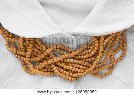 Strings of orange beads on white blouse closeup