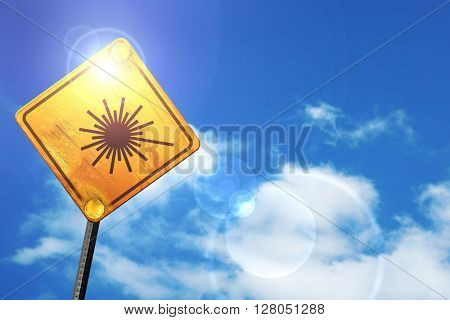 Yellow road sign with a blue sky and white clouds: Laser warning
