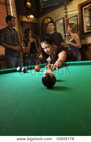Young caucasian woman preparing to hit pool ball while playing billiards.
