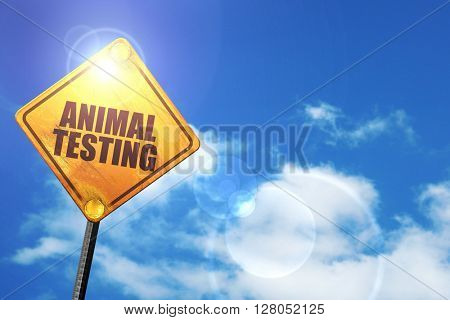Yellow road sign with a blue sky and white clouds: animal testing