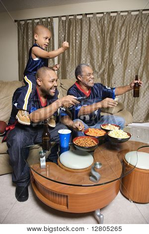 Three male generations of an African-American family watching football game on tv.