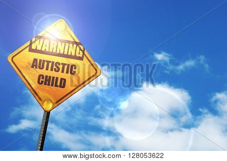 Yellow road sign with a blue sky and white clouds: Autistic chil