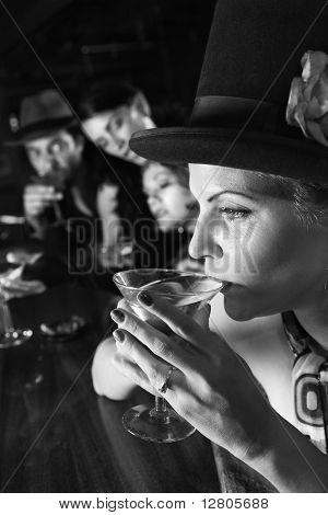 Caucasian prime adult retro female sitting at bar drinking martini.