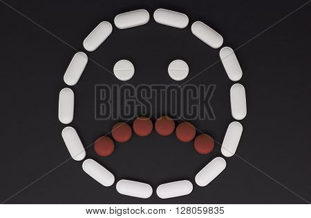 Pills in the form of a frown face on black background
