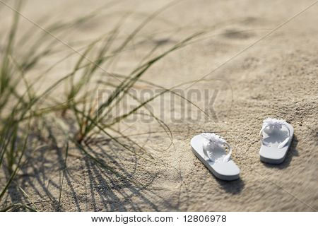 Two white sandals on sandy beach.