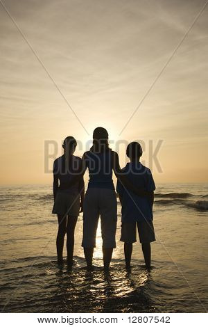 Caucasian mid-adult mother and teenage kids standing silhouetted on beach at sunset.