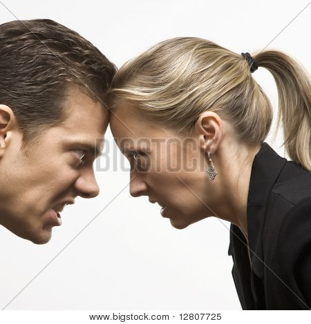 Caucasian mid-adult man and woman with foreheads together staring at each other with hostile expressions.