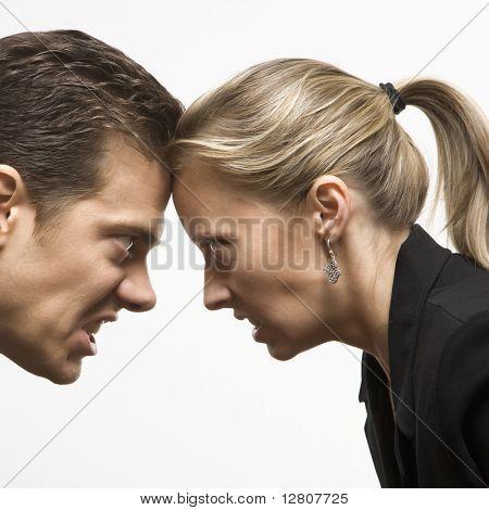 Caucásico mid-adult hombre y mujer con frentes juntos mirando con hostil express