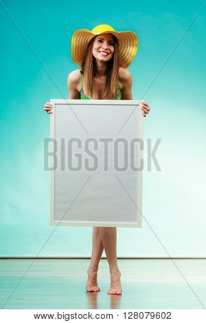 Holidays summer and advertisement concept. Woman wearing yellow hat and bikini holding blank presentation board. Female model posing in full length on blue background.