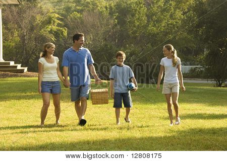 Caucasian family of four walking in park carrying picnic basket.