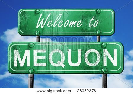 mequon vintage green road sign with blue sky background