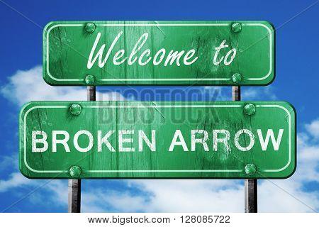 broken arrow vintage green road sign with blue sky background