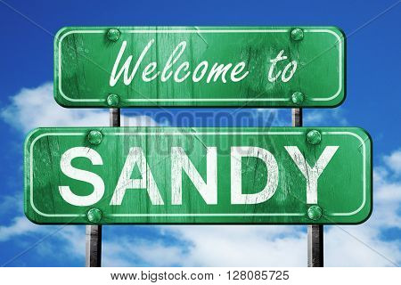 sandy vintage green road sign with blue sky background