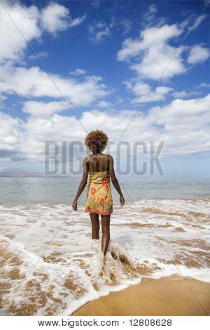Mid schwarz weiblich zu Fuß in Richtung Ozean.