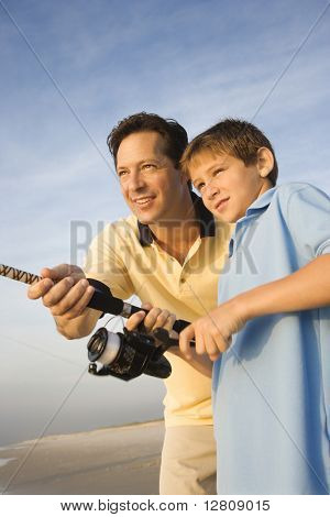 Caucasian mid-adult man shore fishing on beach with pre-teen boy