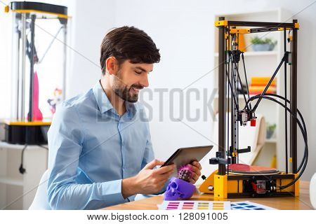Involved in modern world. Cheerful content smiling ma sitting at the table and using tablet while working with 3d printer