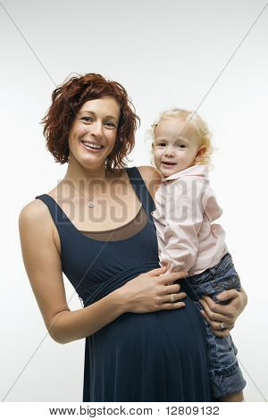 Portrait of Caucasian mid-adult attractive pregnant woman standing, holding female toddler on hip and other hand on belly, looking at viewer and smiling.