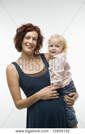 Porträt des kaukasischen Mid attraktive schwangere Frau stehen, Frau Kleinkind auf Hüfte halten ein