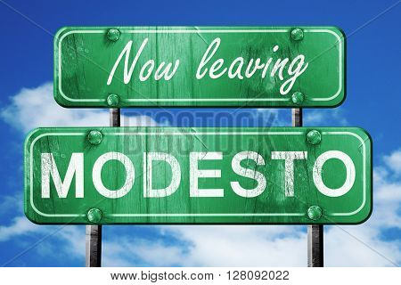Leaving modesto, green vintage road sign with rough lettering