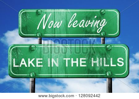 Leaving lake in the hills, green vintage road sign with rough le