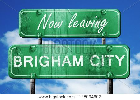 Leaving brigham city, green vintage road sign with rough letteri