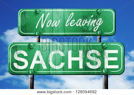 Leaving sachse, green vintage road sign with rough lettering