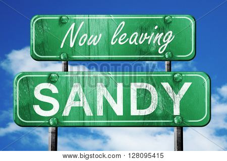 Leaving sandy, green vintage road sign with rough lettering