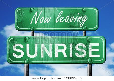 Leaving sunrise, green vintage road sign with rough lettering