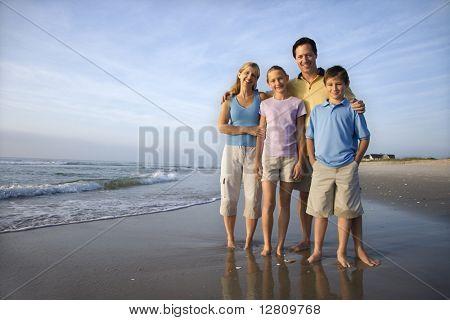 Porträt des kaukasischen Familie von vier posiert am Strand-Blick auf Viewer lächelnd.