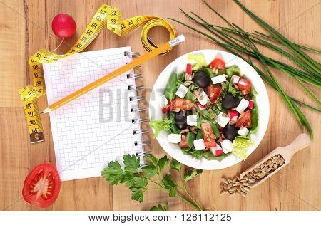 Fresh greek salad with vegetables tape measure and notepad for writing notes concept of healthy nutrition lifestyle and slimming
