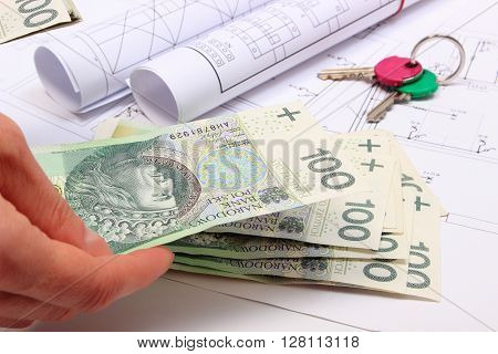 Hand of woman with money home keys and electrical construction drawings of house payment for work