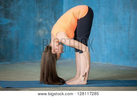 Sporty Beautiful Young Woman Doing Uttanasana Pose
