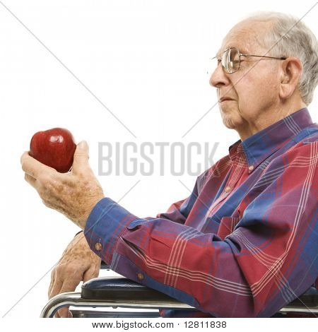 Profile of Caucasion elderly man sitting in wheelchair looking at red apple in his hand.