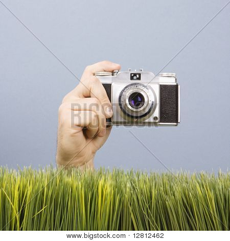 Studio shot of Caucasian male hand holding vintage camera with grass in foreground.