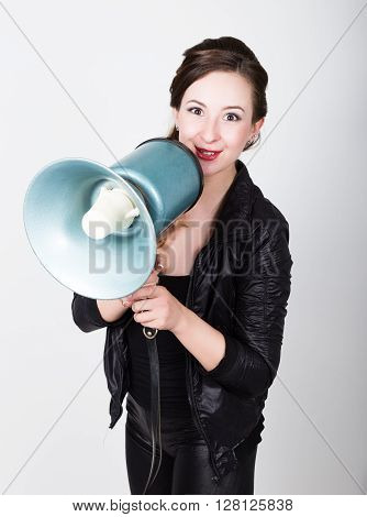 leggy beautiful girl in black skin-tight trousers and jacket, she yells into a bullhorn. Public Relations.