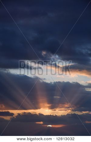 Sunbeams coming through clouds at sunrise over Maui, Hawaii, USA.